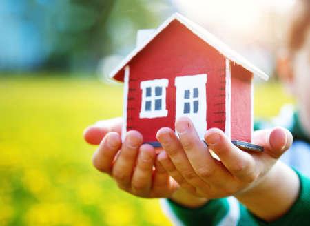 viviendas: Los childs que sostienen la casa roja del modelo de madera