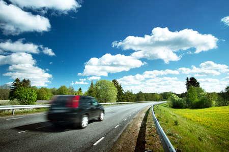 Samochód na drodze asfaltowej w piękny wiosenny dzień na wsi