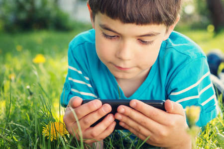 child boy: Child lying on the grass in summer suth mobile phone in summer
