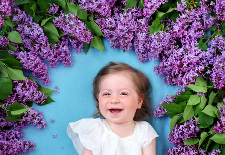 pretty baby: pretty little baby girl lying on blue background with lilac flowers