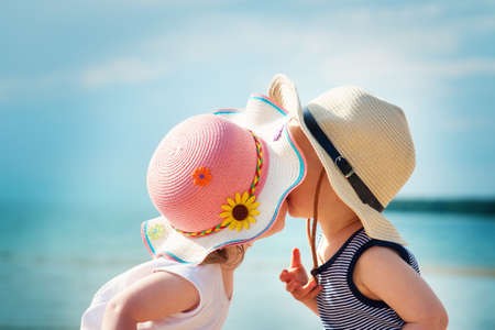 babygirl: Babygirl and babyboy kissing on the beach in straw hats