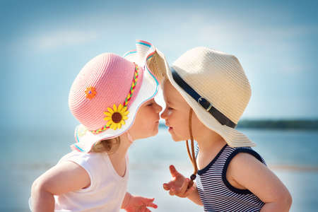 Babygirl and babyboy kissing on the beach in straw hats
