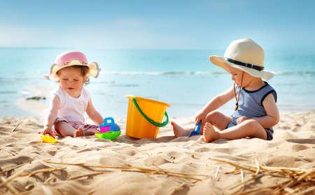 Babygirl en babyboy zittend op het strand in strohoeden Stockfoto