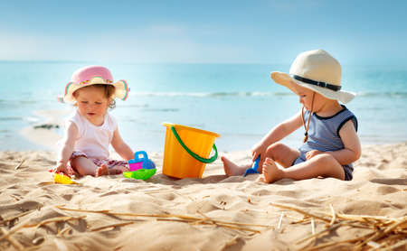Babygirl und babyboy am Strand sitzen in Strohhüte Lizenzfreie Bilder