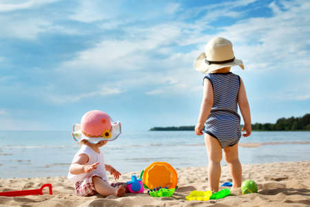 babygirl: Babygirl and babyboy on the beach in straw hats