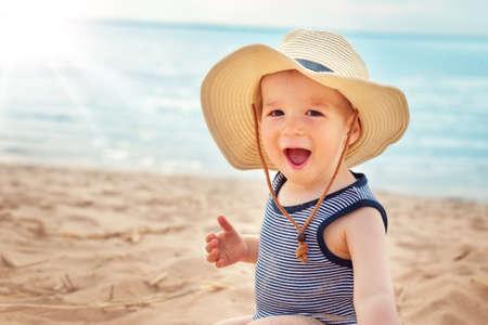 麦わら帽子のビーチで座っている 1 歳の男の子 写真素材