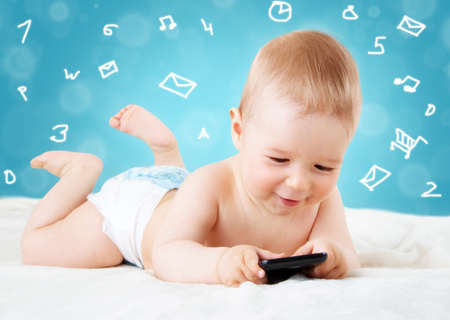 Baby holding a mobile phone on blue background Banque d'images