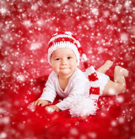 pequeño bebé en sombrero hecho punto blanquito rojo en manta roja