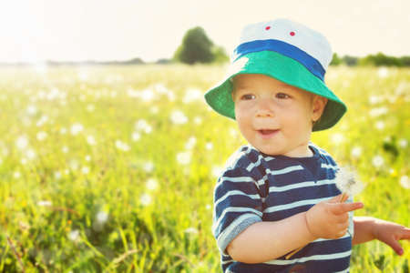 Baby boy sitting in grass on the fieald with dandelions at sunnysummer evening