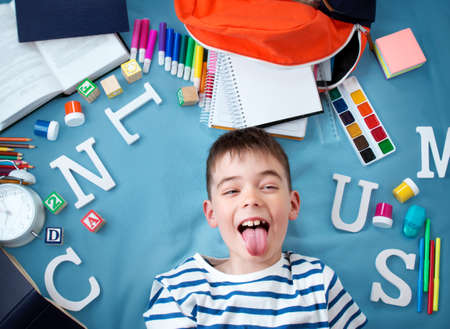 blue blanket: child lying on blue blanket with various school accessories