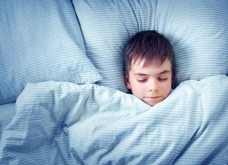 zeven jaar oude kind liggend in het bed met blauwe beddengoed