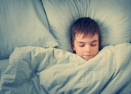 7 year old boys: seven years old child lying in the bed with blue bedding