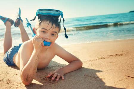 flippers: Niño acostado en la playa con la máscara de la natación y aletas. Chico de vacaciones en el mar