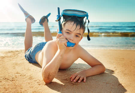 boy kid: Child lying on the beach with swimming mask and flippers. Boy on vacation at sea