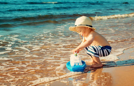 Baby boy playing with ship toy at sea. Child os on vacation in summer at the beach on vacations Archivio Fotografico
