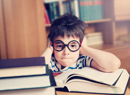 seven years: seven years old child reading a book at home Stock Photo
