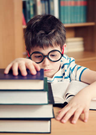 boy book: seven years old child reading a book at home Stock Photo