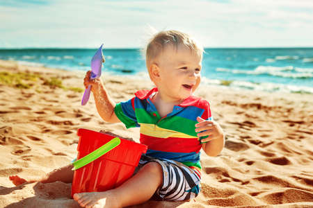 1 year old: one year old boy smiling at the beach. Child on vacations at sea