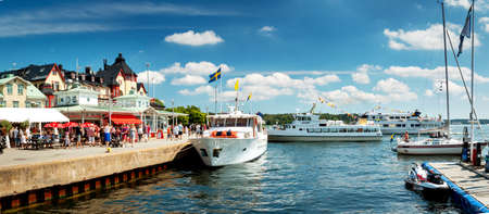 archipelago: VAXHOLM, SWEDEN - JUNE 25, 2016: Cruise boats at little cosy island Vaxholm near Stockholm