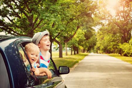 Kinder schauen aus dem Fenster aus einem Auto. Jungen gehen am Sommertag in den Urlaub Standard-Bild - 61105311