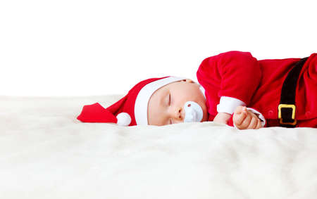 little baby sleeping in red hat on white blanket. Eight month old child in santa costume Stock Photo