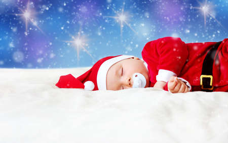 christmas light: little baby sleeping in red hat on white blanket. Eight month old child in santa costume Stock Photo