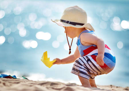 one year old boy playing at the beach in straw hat. Child with a paper ship at sea