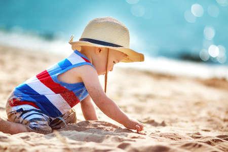 Egy éves fiú játszik a strandon szalmakalapot. Gyermek családi vakáció a tengeren