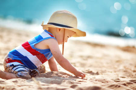 one year old boy playing at the beach in straw hat. Child on family vacations at sea 免版税图像