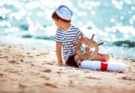 seven years: seven years old boy playing at the beach in sailor hat. Child with a steering wheel at sea