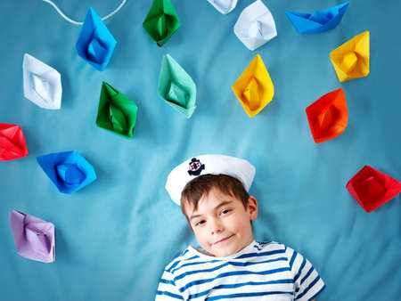seven years: seven years old boy playing in sailor hat. Child withpaper ships on blue background Stock Photo