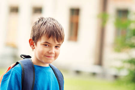 7 year old boys: Boy with rucksack infront of a school building. Child with a backpack