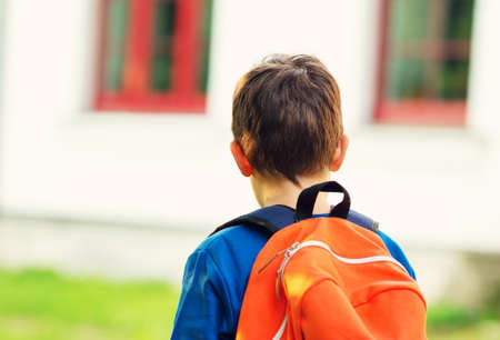 first year student: Boy with rucksack infront of a school building. Child with a backpack