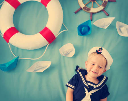 baby toys: two years old boy playing in sailor hat. Child with paper ships on blue background