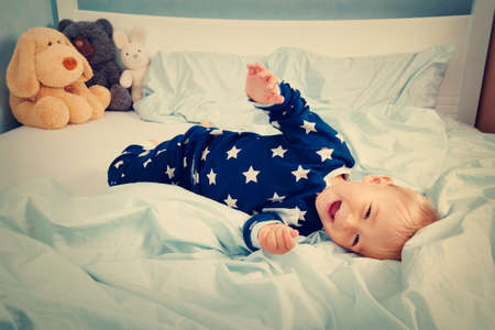 one year: One year old baby in pyjamas lying in the bed with blue bedding Stock Photo