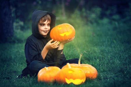 skeleton costume: Child in scary costume holding pumpkin ln. Child in halloween outfit at night
