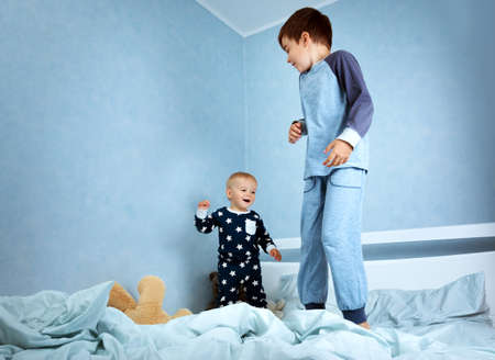 2 years old: One year old baby in pyjamas lying in the bed with blue bedding Stock Photo
