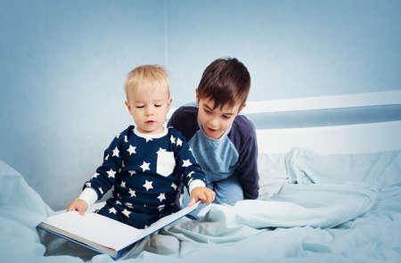 兄弟のパジャマでベッドに座って、本を読んで 写真素材 - 63246249