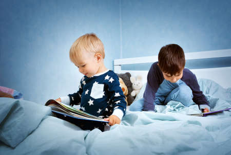 Brothers sitting in the bed in pyjamas and reading books