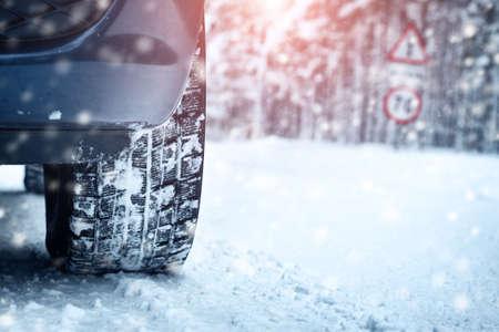Autobanden op de winter weg bedekt met sneeuw. Voertuig op besneeuwde steegje in de ochtend bij sneeuwval