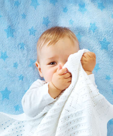 One year old baby lying on blue towel with stars. Child hiding under blanket