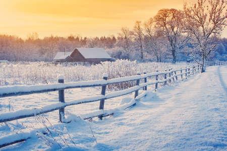 granja: Casa rural con una valla en invierno. Pueblo después de las nevadas