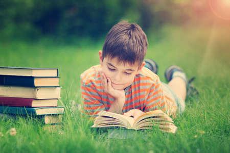 7 Jahre altes Kind ein Buch zu lesen auf dem Rasen lag
