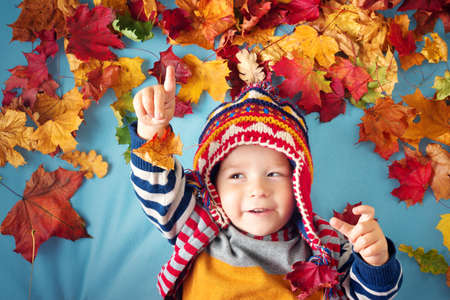 two years old boy dreaming in autumn. Child in hat and scarf playing with maple leaves on blue background Stok Fotoğraf