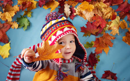 two years old boy dreaming in autumn. Child in hat and scarf and maple leaves on blue background