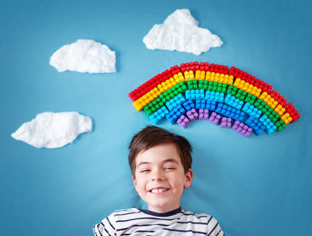 Child lying on blue blanket with rainbow and clouds Stock Photo