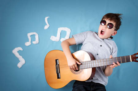 happy seven years old boy on blue blanket background with acoustic guitar and musical notes. Young guitarist singing song Foto de archivo