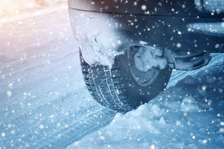snow  snowy: Car tires on winter road covered with snow. Vehicle on snowy alley in the morning at snowfall