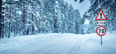 snowscape: winter panorama on the road through coniferous forest. Road caution sign in forest landscape