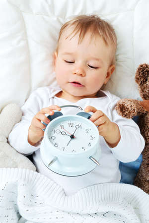 one year old: One year old baby lying in bed with alarm clock